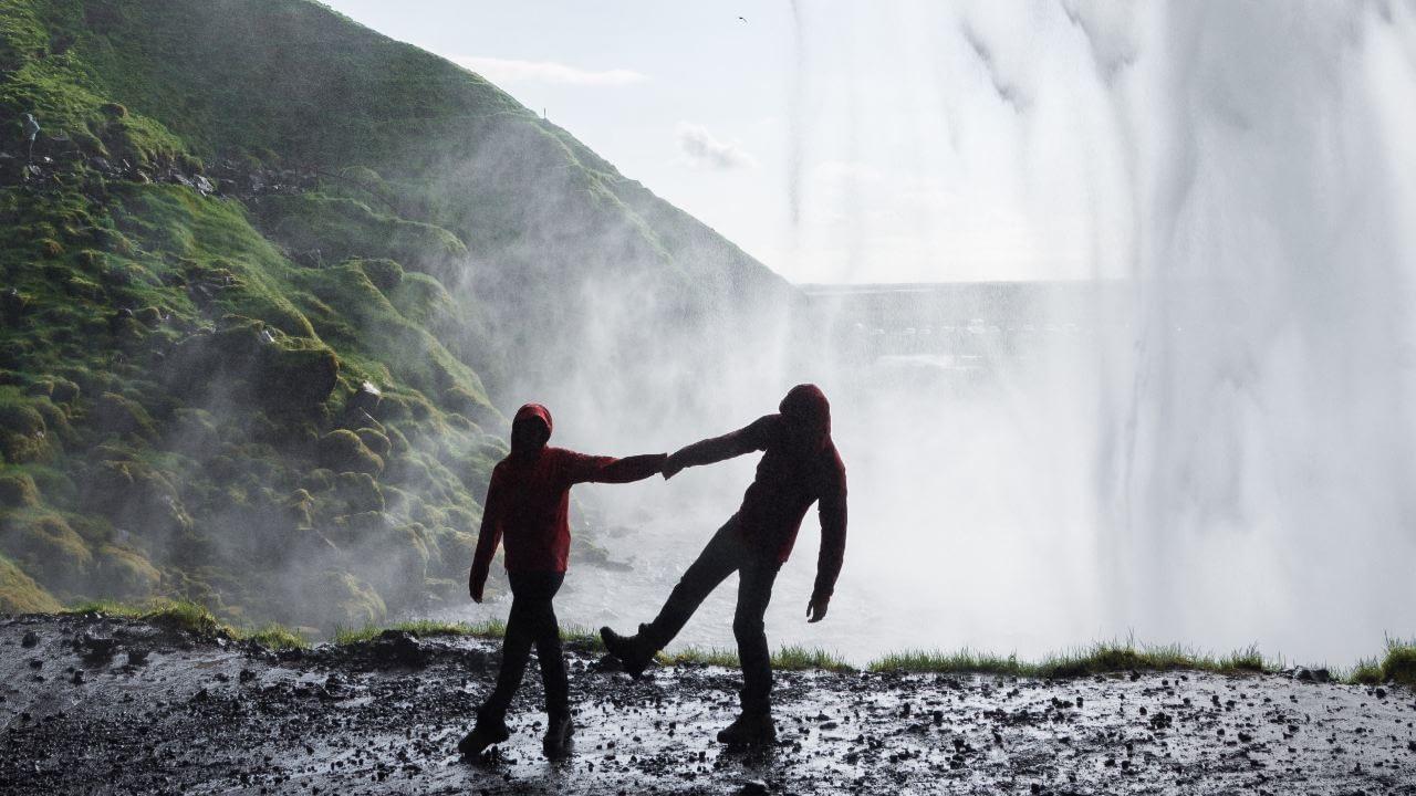 Fólk að leiðast við foss. Seljalandsfoss. Dagur íslenskrar náttúru. Við erum náttúran.