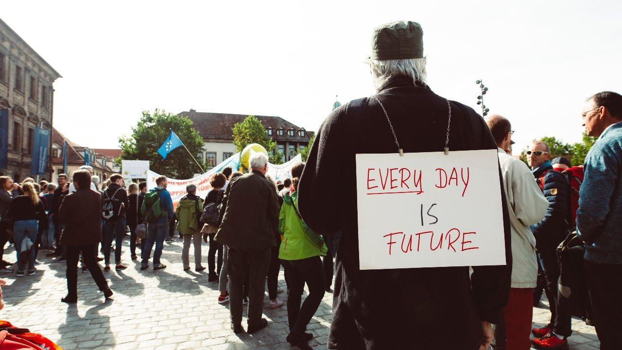 "Sign on back of a man. Sign says ""everyday is future"" Hafðu áhrif."
