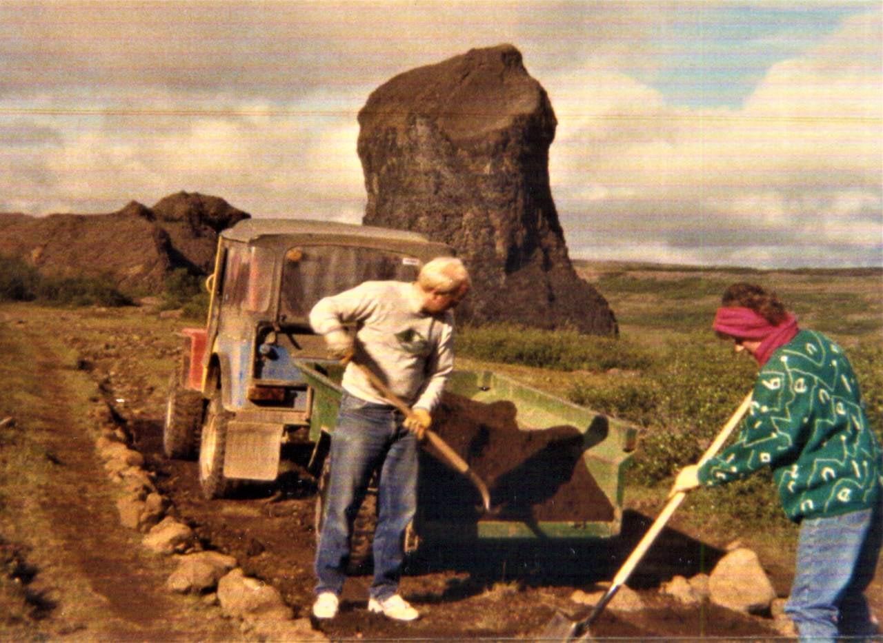 Kona og karl með skoflur að moka sand úr kerru á veg. Sjálfboðaliðasamtök um náttúruvernd leggja göngustíg við Hljóðakletta við Jökulsárgljúfur árið 1986.