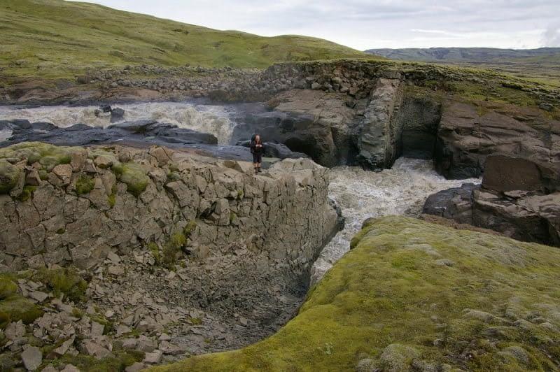 Ferðamaður stendur við Lambhagafoss og flúðir í Hverfisfljóti